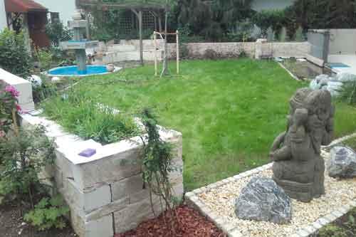 Garteneinfassung mit Natursteinelementen und Statuen